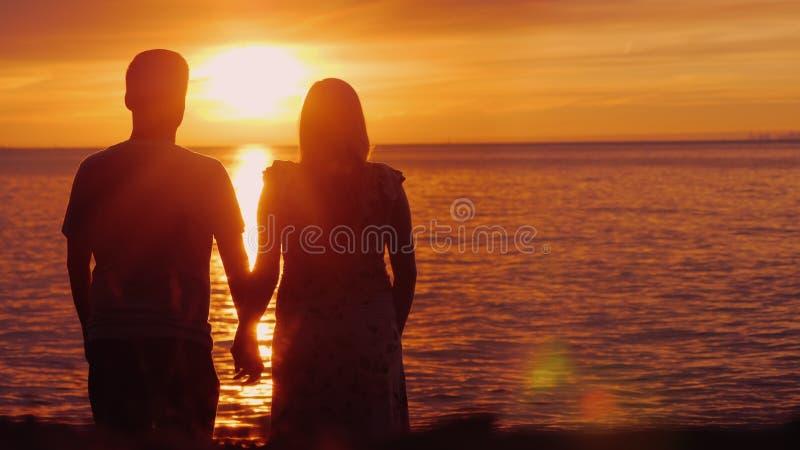 Det romantiska mång--person som tillhör en etnisk minoritet paret beundrar den sceniska solnedgången över havet Rymma h?nder, bak arkivbild