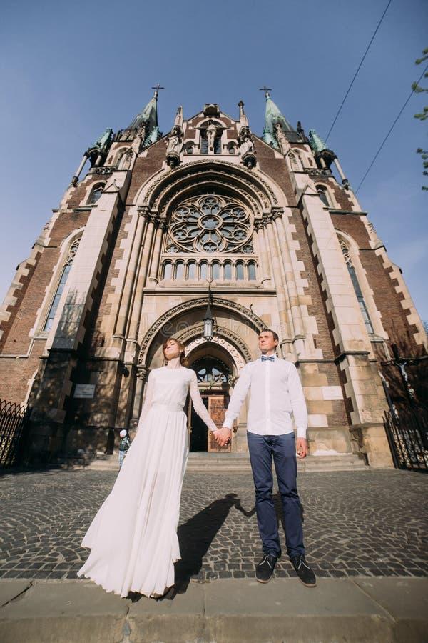 Det romantiska paret, nygift personvalentynes som poserar att rymma, räcker nära gammal gotisk kyrka fotografering för bildbyråer