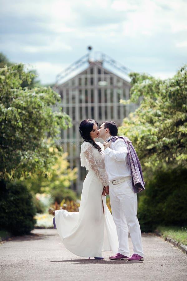 Det romantiska sagagifta paret i vit beklär att kyssa i gummin arkivbilder