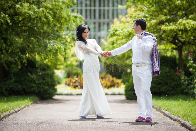 Det romantiska sagagifta paret i vit beklär innehavhänder royaltyfria foton