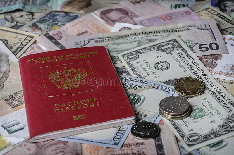 Det ryska passet på en hög av utländska valutor arkivfoton