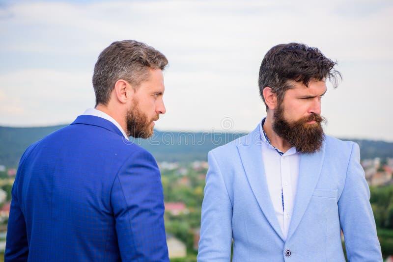Det säkra tecknet bör du inte lita på affärspartnern Står formella dräkter för män säkert bakgrund för blå himmel entreprenör royaltyfri fotografi