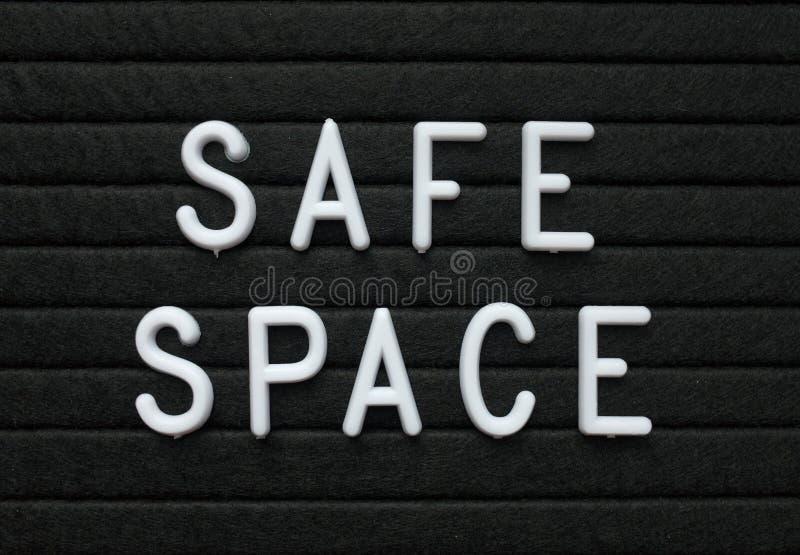 Det säkra utrymmet för ord i vita plast- bokstäver på ett bräde för svart bokstav arkivfoton