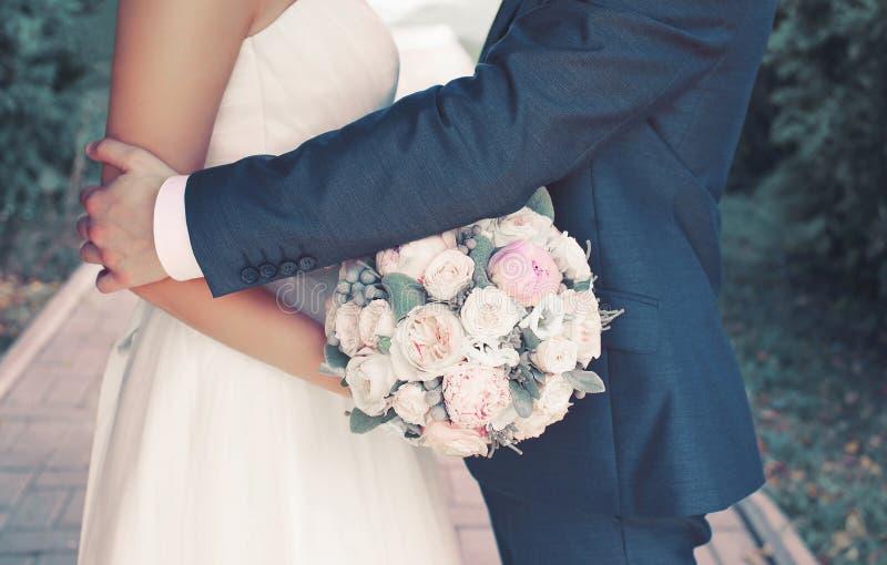 Det söta bröllopparet med den försiktiga buketten av pioner blommar, den sinnliga brudgummen som kramar den älskvärda bruden royaltyfri foto