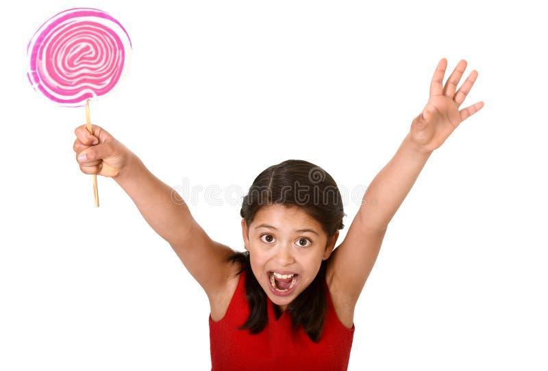 Det söta härliga latinska kvinnliga barnet som rymmer stora rosa färger, röra sig i spiral klubbagodisen royaltyfria bilder