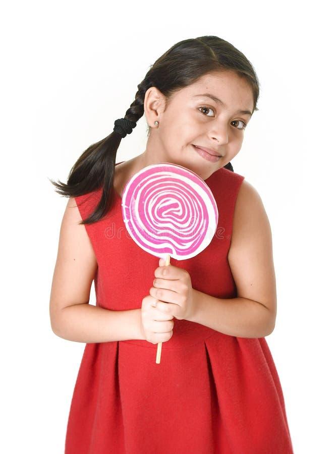 Det söta härliga latinska kvinnliga barnet som rymmer stora rosa färger, röra sig i spiral klubbagodisen royaltyfria foton