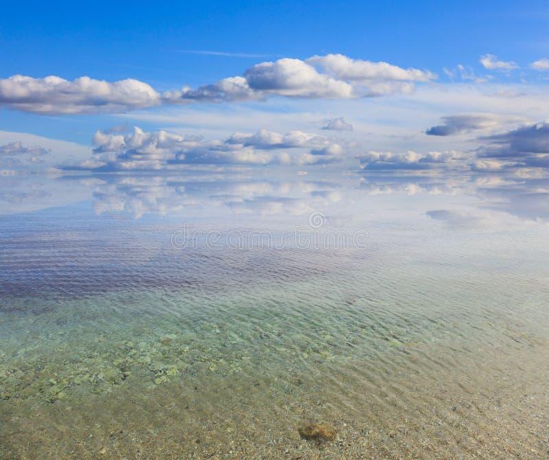 Det sandiga lugna havet, blå himmel med få fördunklar bakgrund, det genomskinliga havet för crystal akvamarin arkivbild