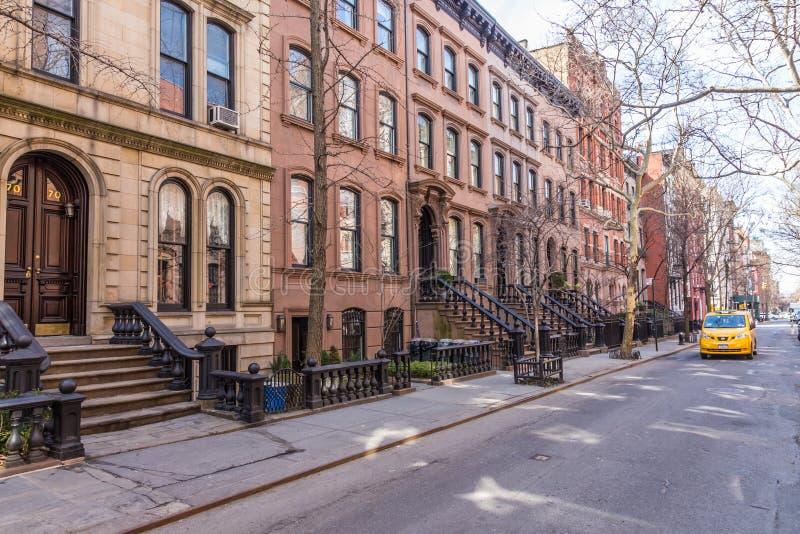 Det sceniska trädet fodrade gatan av historiska rödbrun sandstenbyggnader i den västra bygrannskapen av Manhattan i New York City royaltyfri foto