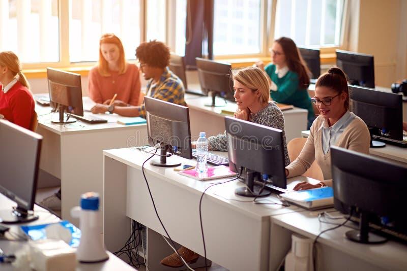 DET seminarium på universitetet Grupp av studenter på grupp med datoren arkivfoto