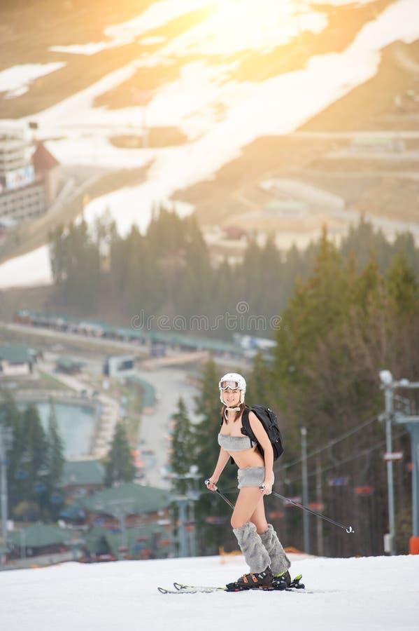 Det sexiga härliga nakna flickaanseendet på den snöig lutningen av berget, bärande hjälm, skidar och vandrar royaltyfria foton