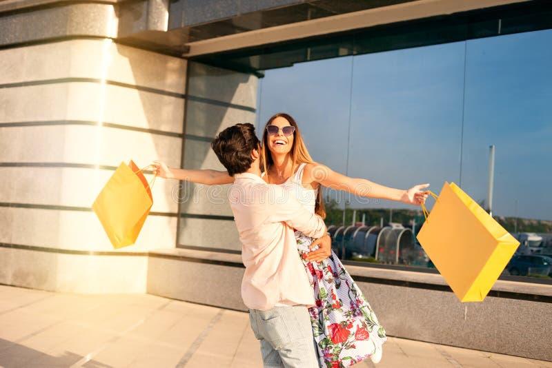 Det shopping för ` s och gyckeltid, ungt älskvärt par som är lyckligt efter fotografering för bildbyråer