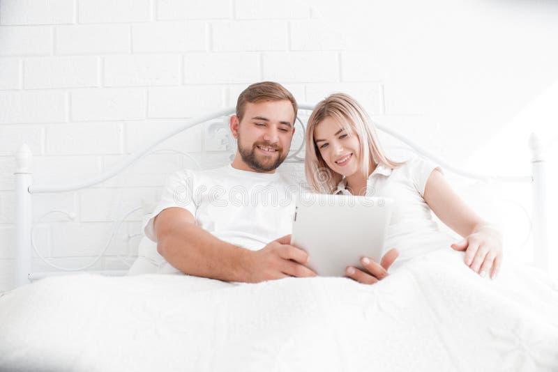 Det sinnliga barnet kopplar ihop tillsammans i säng Lyckliga par i sovrum på en vit bakgrund royaltyfri foto