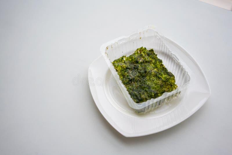 Det sista stycket av korean stekte havsväxt i plast- behållare av packi royaltyfri foto