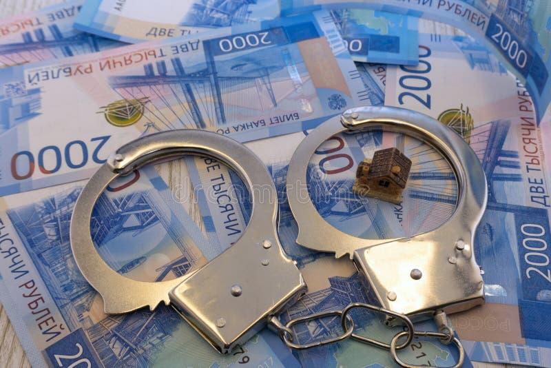 Det små leksakhuset och handbojor är lögner på en uppsättning av gröna monetära valörer av 100 euro Mycket pengar bildar en oändl arkivfoton