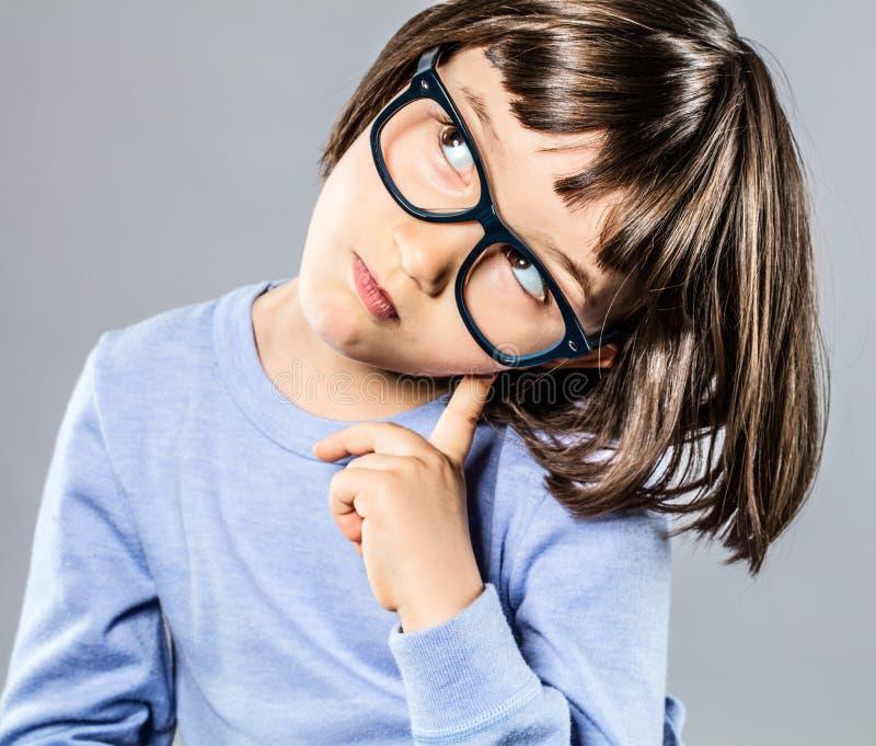 Det smarta unga barnet med allvarligt rymma för glasögon går mot intelligens royaltyfria bilder