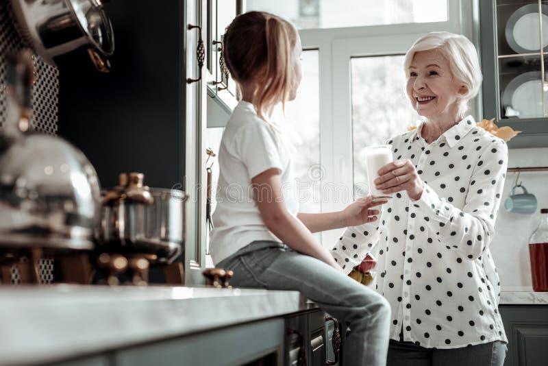 Det snälla älska farmoranseendet i köket och att erbjuda mjölkar till flickan arkivfoton