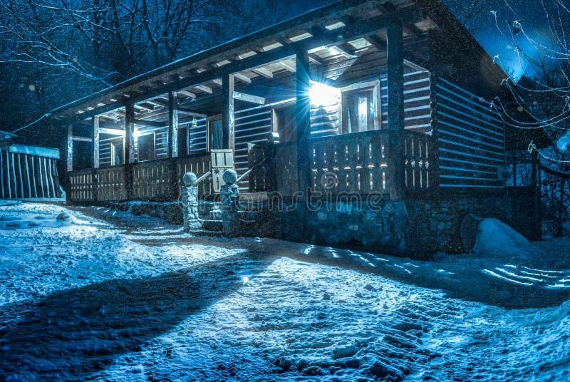 Det snöar över chalet vid natt royaltyfria foton