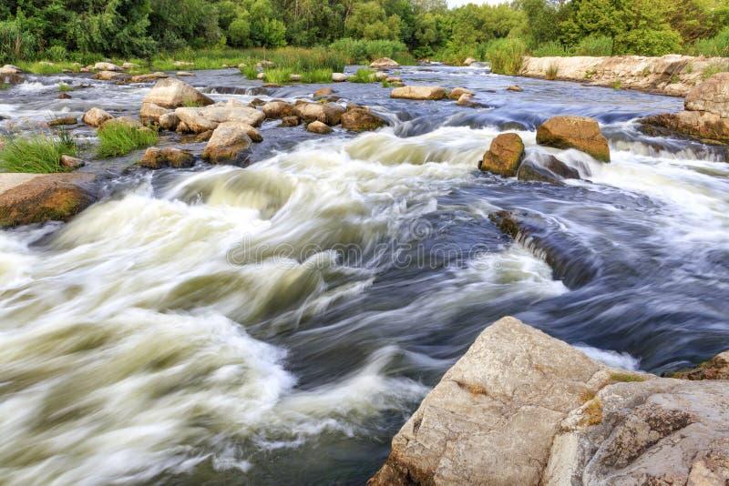 Det snabba flödet av floden i suddigheten, de steniga kusterna, stenblock och forsar som är ljusa - grön vegetation på andra sida arkivbild