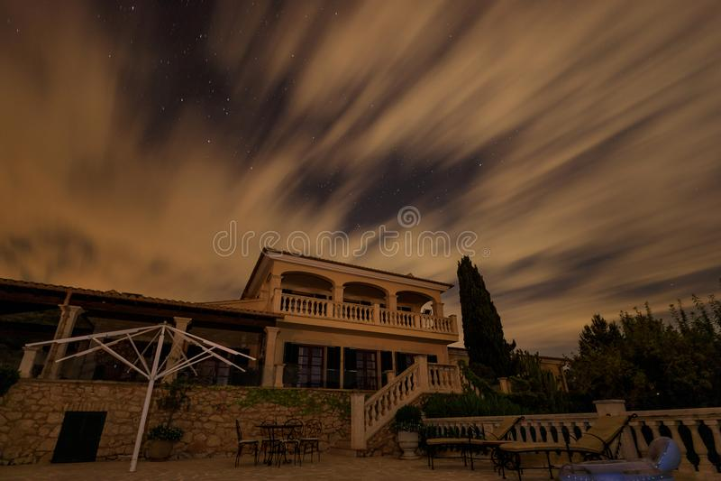 Det spanska huset under molnig natthimmel arkivfoto