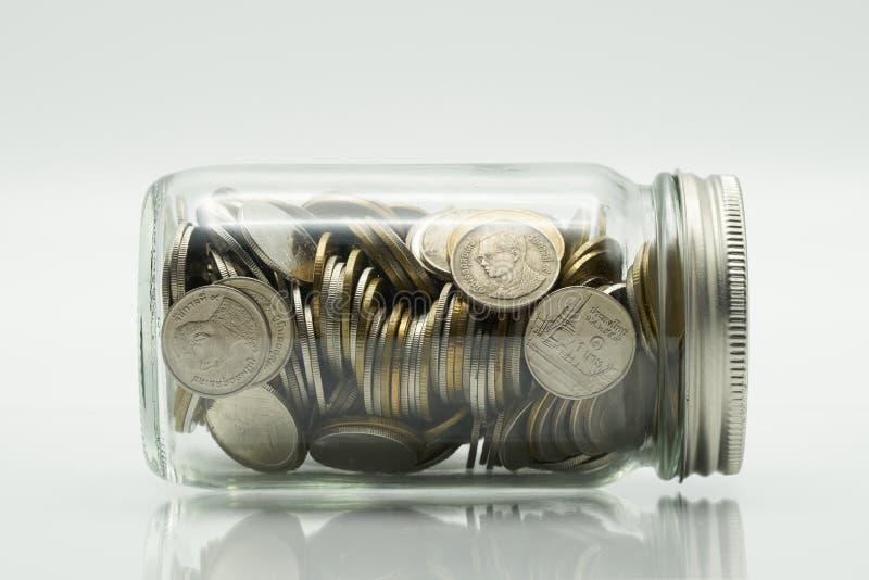 Det sparande pengarbegreppet av att samla myntar thailändska pengar i en glasflaska på isolatvitbakgrund som bakgrundsaffärsconce royaltyfri foto