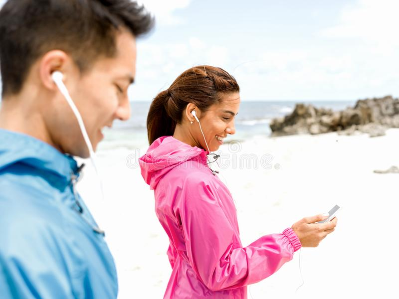 Det sportiga barnet kopplar ihop med hörlurar på havskusten arkivfoton