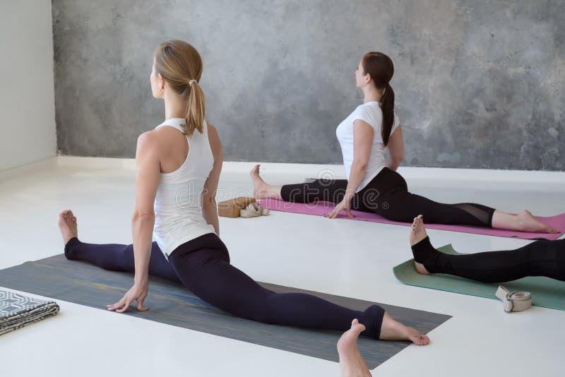 Det sportiga caucasian folket som gör yoga Hanumanasana, poserar och att utarbeta inomhus arkivfoton