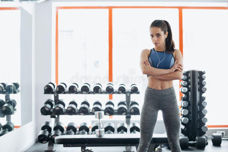 Det sportiga kvinnaanseendet med armar korsade i konditionidrottshall royaltyfri foto