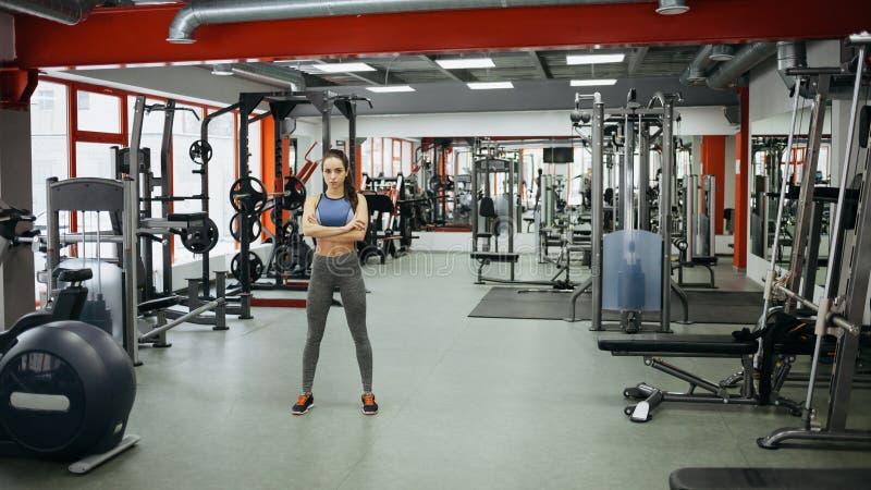 Det sportiga kvinnaanseendet med armar korsade i konditionidrottshall royaltyfria foton