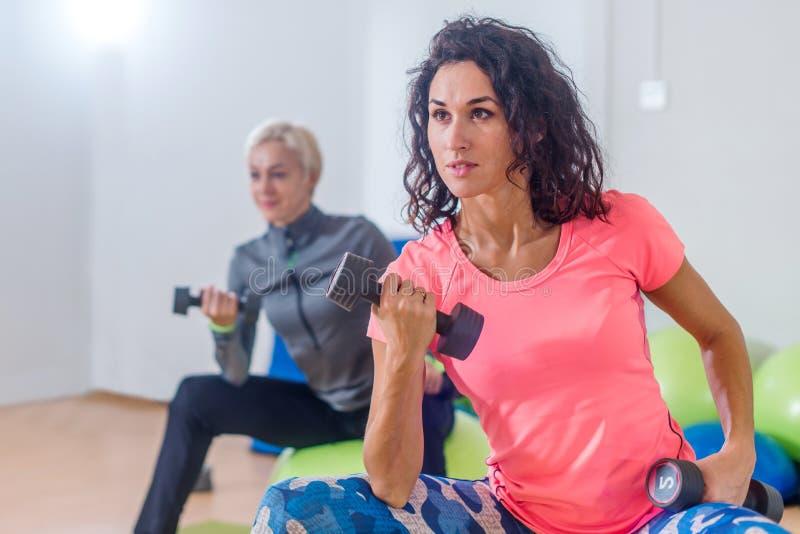 Det sportiga slanka kvinnadeltagandet i idrottshallkonditiongrupp som övar sammanträde på physioballs som gör växlad biceps, krul fotografering för bildbyråer