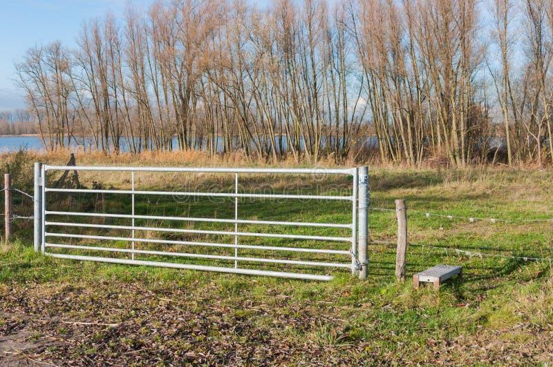 Det stängda galvaniserade staket i ett lantligt landskap arkivbilder