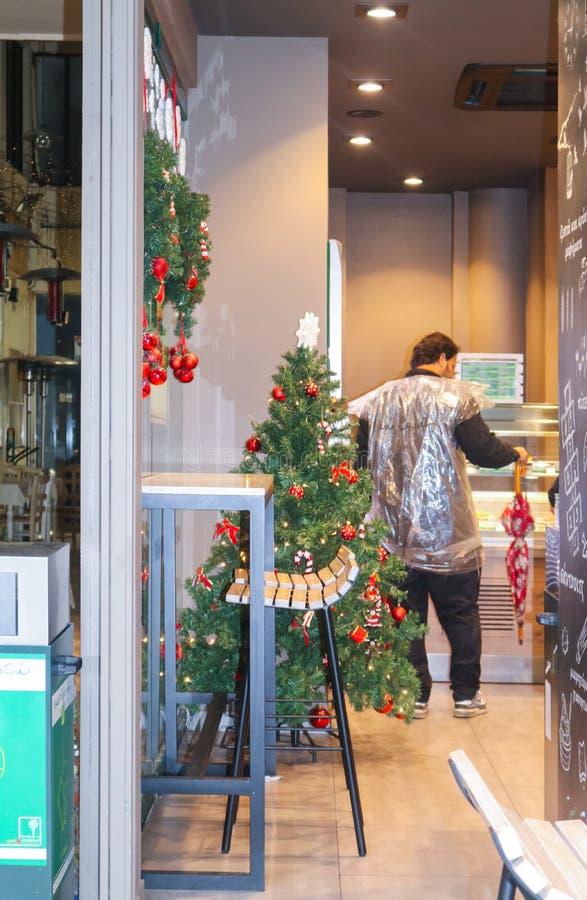 Det stads- kafét dekorerade för jul med kunden med det plastpåseregnrocken och paraplyet på räknaren Athen Grekland 1-04-2018 arkivbilder