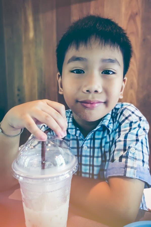 Det stiliga asiatiska barnet som ler med kallt, mjölkar efter hans lunch slump arkivfoto