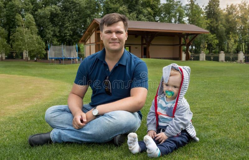 Det stiliga barnet avlar sammanträde med hans 9 månader gammal son på gräs royaltyfri bild