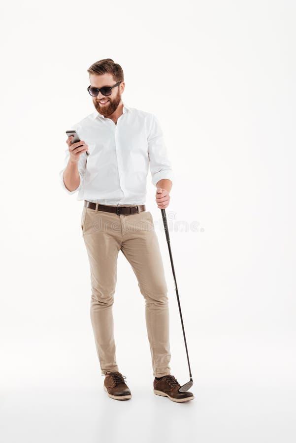 Det stiliga barnet uppsökte mannen som står över den vita väggen med golfstick royaltyfri bild