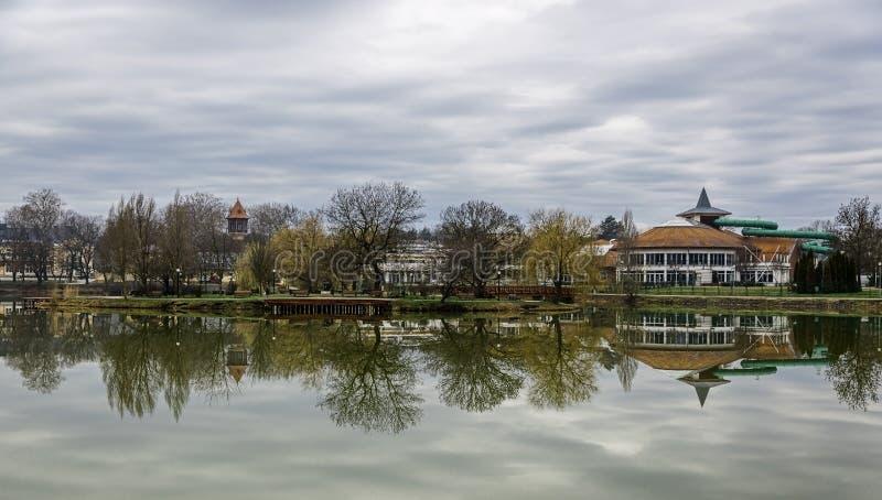 Det stillsamma landskapet med sjön, hus, molnig himmel och träd reflekterade symmetrically i vattnet Nyiregyhaza Ungern fotografering för bildbyråer