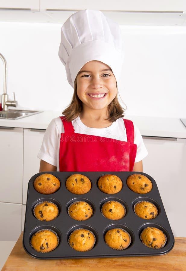 Det stolta kvinnliga barnet som framlägger hennes själv gjorde muffinkakor som lär baka bärande rött le för förkläde- och kockhat royaltyfri fotografi