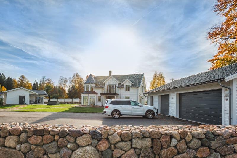 Det stora familjhuset med det dubbla den formatgaraget och bilen parkerade framme Bostads- hus med den konkreta körbana- och ingå arkivbilder