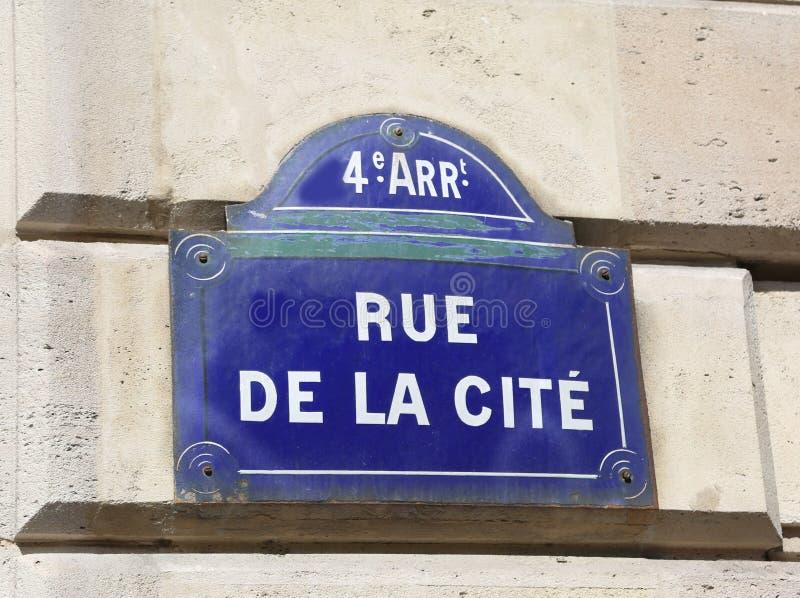 Det stora tecknet med text den Rue de la Cite betyder vägen av staden in arkivbilder