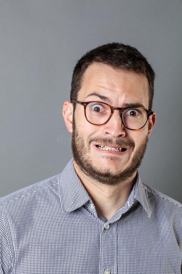 Det stressade barnet uppsökte ut entreprenören med glasögon som maler tänder arkivbild