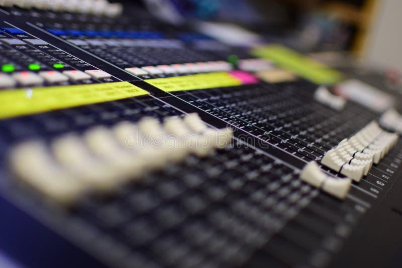 Det suddiga generiska fotoet av den Soundboard för TV-sändning för konsertmusik blandaren och utjämnaren med glidare blir grund D royaltyfria bilder