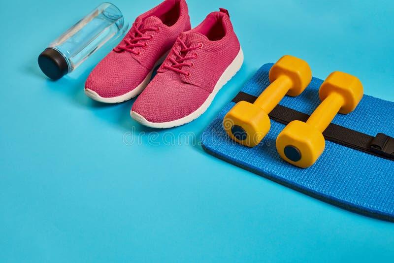 Det sunda begreppet, bantar plan med sportskor och flaskan av vatten och hantlar på blå bakgrund, sund mat och arkivfoto