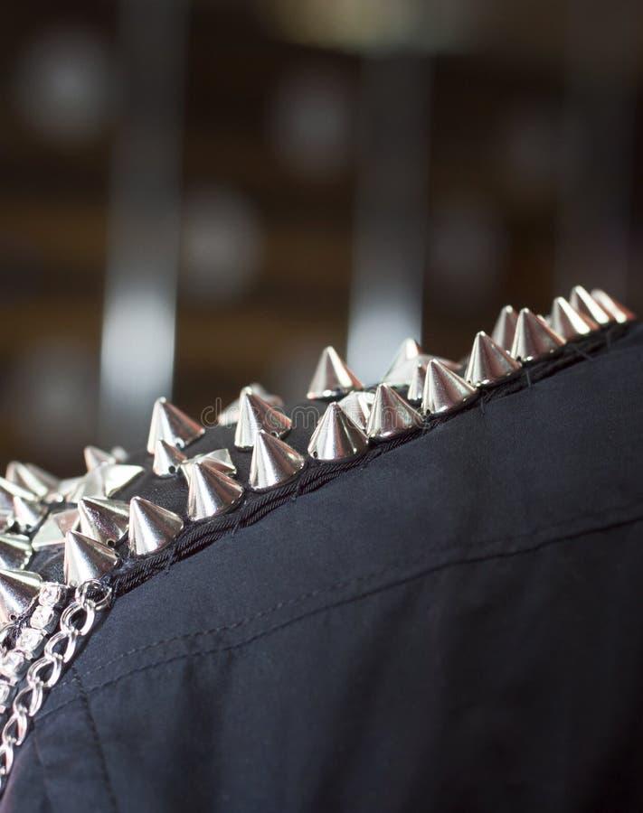 Det svarta omslaget, metallgrova spikar på skuldran, vaggar musikern, närbild arkivfoton
