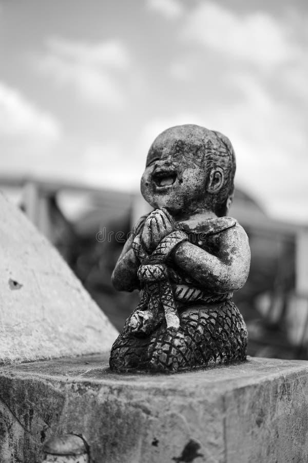 Det svartvita brutna stenleendet och den lyckliga ungestatyn royaltyfri bild