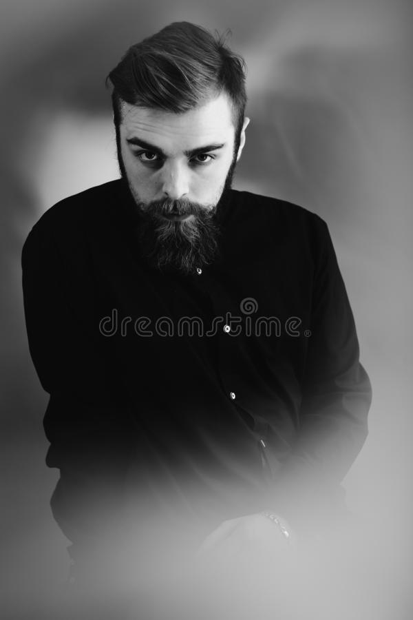 Det svartvita fotoet av en stilfull man med ett iklädda skägg och stilfull frisyr den svarta skjortan står i dimman arkivfoto