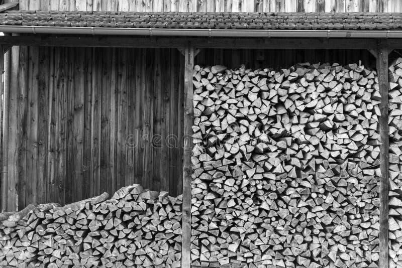 Det svartvita fotoet av wood journaler lagrar klart för bruk i G arkivfoto