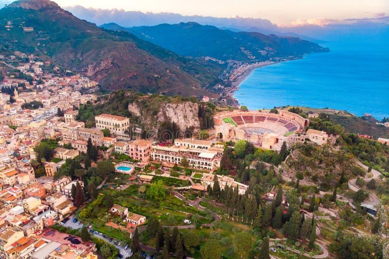Det Taormina landskapet och fördärvar av teatern, den Sicilien Italien solnedgången, vulkan Etna i moln Flyg- b?sta sikt arkivfoto