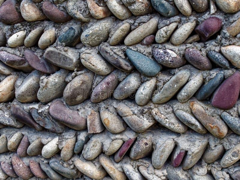 Det texturerade fragmentet av graniten stenar dengrå färger fasaden av väggen arkivfoto