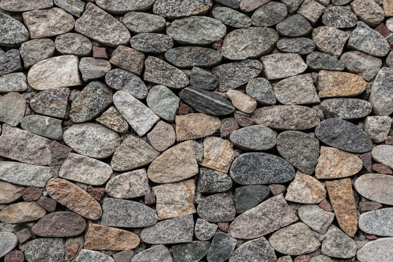 Det texturerade fragmentet av graniten stenar dengrå färger fasaden av väggen royaltyfri fotografi