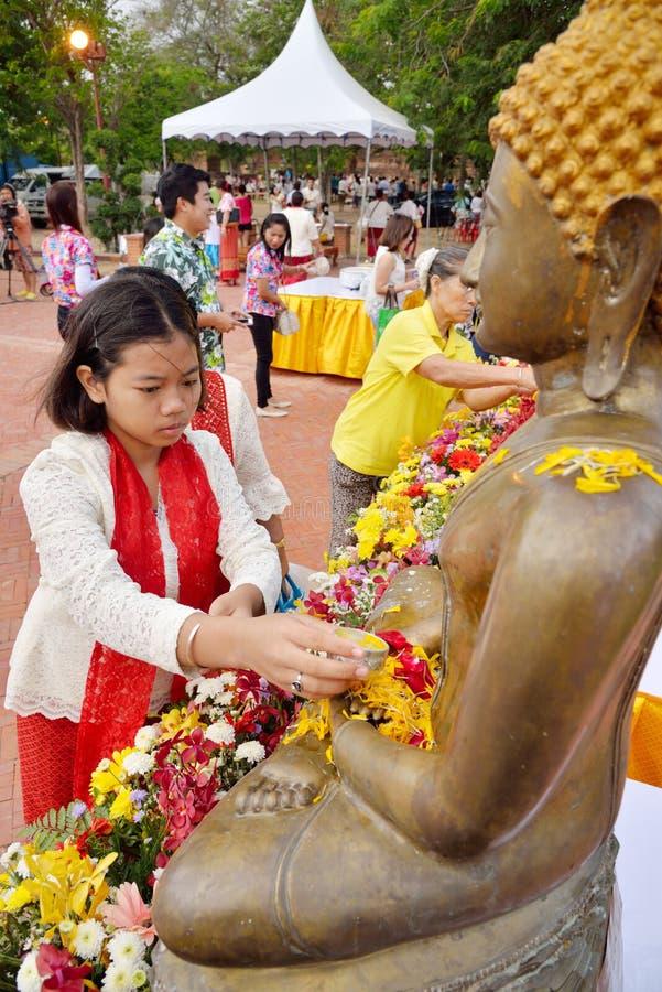 Det thailändska folket bevattnar att hälla till Buddhastatyn in arkivbilder