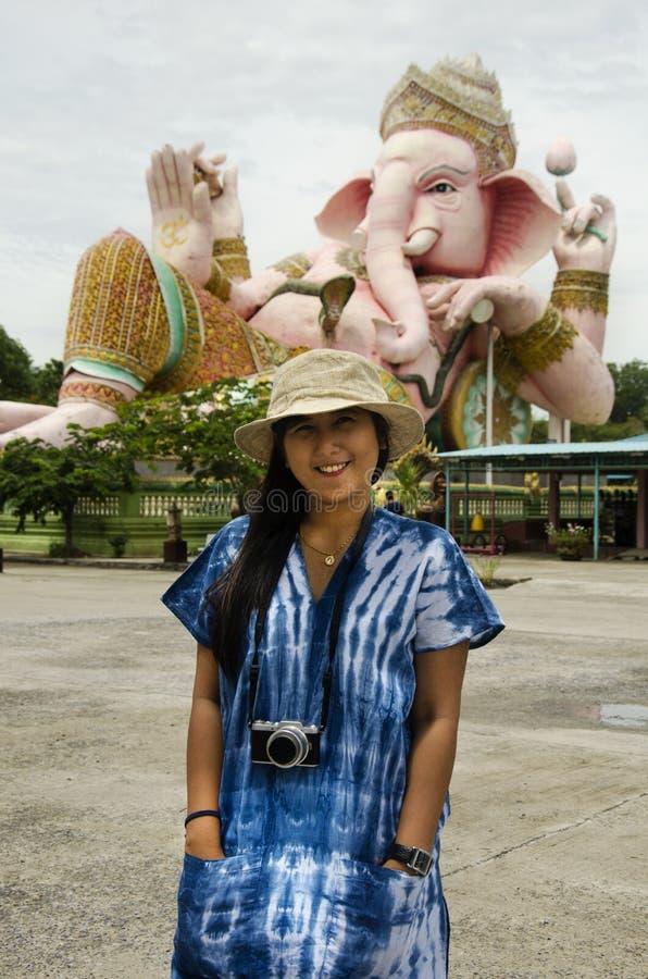 Det thailändska kvinnaloppet och att posera för tar fotoet med den stora Ganesh statyn royaltyfria bilder